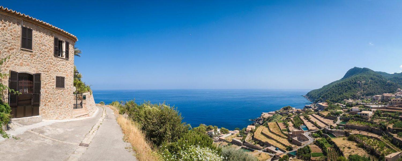 Traditional villa overlooking terraced vineyard and idyllic blue sea, Majorca, Spain.